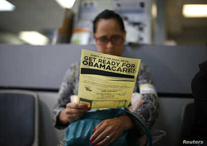 FILE - Arminda Murillo, 54, reads a leaflet on Obamacare at a health insurance enrollment event in Cudahy, Calif., March 27, 2014.