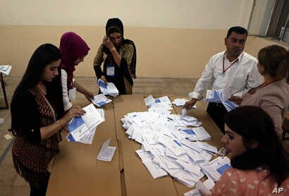 Election officials count ballots after the polls close in the controversial Kurdish referendum on independence from Iraq, in Irbil, Iraq, Sept. 25, 2017.