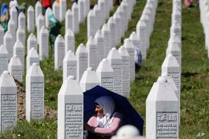 A Bosnian Muslim woman protects herself from the sun during a funeral ceremony for dozens of newly identified victims of the 1995 massacre, at the memorial centre of Potocari near Srebrenica, 150 kms north east of Sarajevo, Bosnia, July 11, 2017.