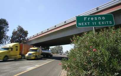 FILE - Trucks fly by a Fresno sign on California State Route 99, Aug. 23, 2011, in Fresno, Calif.