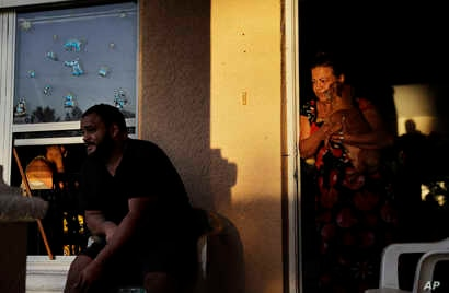 FILE - Sandra Pagan, right, looks out from her front door while escaping the heat inside her home with her dog Goldo, nephew Misael Fernandez, center, and niece Lorraene Andaluz, in window at left, after Hurricane Irma flooded their neighborhood leav...