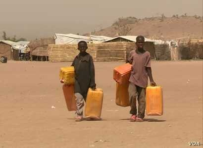 Children treck long distances to fetch water, near Minawao refugee camp in northern Cameroon, Feb. 9 2018. (M. Kindzeka/VOA)