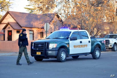 Sheriff's deputy guards the entrance to Aztec High School in Aztec, New Mexico, following a deadly shooting on campus, Dec. 7, 2017..