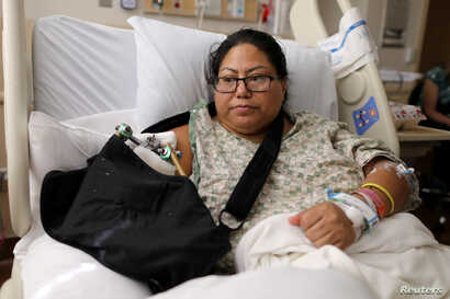 FILE - Paola Bautista, 39, of Fontana, California, sits in her bed at Sunrise Hospital & Medical Center in Las Vegas, Nevada, Oct. 4, 2017. She was one of those shot Oct. 1 at the Route 91 music festival next to the Mandalay Bay Resort and Casino in ...