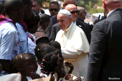Pope Francis greets internally displaced people sheltering on the grounds of the Saint Sauveur church, during his visit in the capital Bangui, Central African Republic, Nov. 29, 2015.