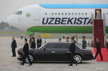 FILE - Chinese guards walk along with Uzbekistan's President Shavkat Mirziyoyev's car in Qingdao city, Shandong province, China, June 8, 2018.