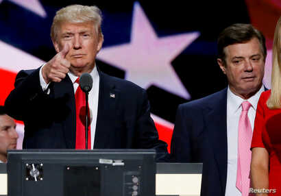 FILE - Republican presidential nominee Donald Trump gives a thumbs up as his campaign manager Paul Manafort looks on during Trump's walk through at the Republican National Convention in Cleveland, July 21, 2016.