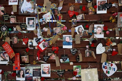 FILE - Photos and notes adorn a wall at the Las Vegas Community Healing Garden in Las Vegas, Oct. 16, 2017. The garden was built as a memorial for the victims of the mass shooting in Las Vegas.