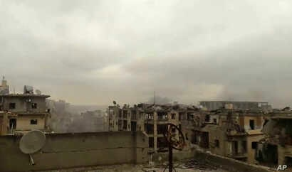 In this still image taken from video released by a Syrian activist Wednesday smoke rises in the distance alongside the sound of heavy bombardment in east Aleppo, as a cease-fire deal to evacuate the city's residents begins to collapse. (Salah Ashka...