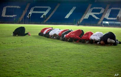 Players of the Egyptian national soccer squad and team officials pray at Cairo's stadium, Egypt, Monday, Nov. 6, 2017, before training to prepare for their Nov. 12 away game against Ghana, in the last African Group E World Cup qualifier.