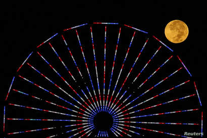 """The moon is pictured behind a ferris wheel on the pier in Santa Monica, California after a total lunar eclipse, also known as a """"blood moon"""", October 8, 2014."""