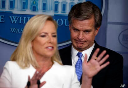 FBI Director Christopher Wray listens as Secretary of Homeland Security Kirstjen Nielsen speaks during the daily press briefing at the White House, Aug. 2, 2018, in Washington.