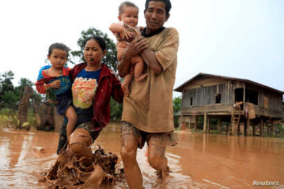 Parents carry their children as they leave their home during the flood after the Xe Pian Xe Namnoy hydropower dam collapsed in Attapeu province, Laos, July 26, 2018.