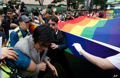 An anti-homosexuality protester, left, who tries to block a parade is taken away by police during the Korea Queer Culture Festival in Seoul, South Korea, June 11, 2016.