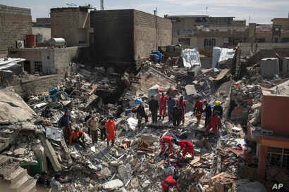 FILE - Civil protection rescue teams work on the debris of a destroyed house to recover the body of people killed during fighting between Iraqi security forces and Islamic State militants on the western side of Mosul, Iraq, March 24, 2017.