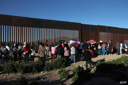 Residents of Anapra, a neighborhood on the outskirts of Ciudad Juarez in Mexico, gather next to the border fence during a prayer with priests and bishops from Mexico and the United States on Feb. 26, 2019.