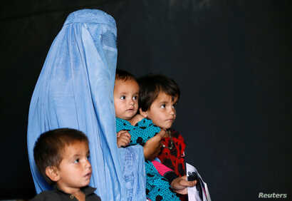 FILE - An Afghan family, returning from Pakistan, watch a short video clip about mines during a mines and explosives awareness program at a United Nations High Commissioner for Refugees (UNHCR) registration centre in Kabul, Sept. 27, 2016.