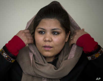 FILE - Afghan women's rights activist Wazhma Frogh adjusts her scarf during an interview in her office in Kabul, Afghanistan, March 5, 2014. A gender and development specialist and human rights activist, Frogh says for Afghan women, the successes a...
