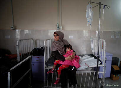 A sick Palestinian girl is held by her mother inside a room at the Durra hospital in Gaza City, Feb. 6, 2018.