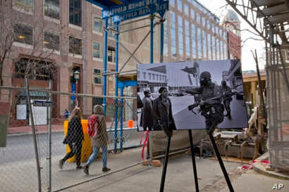 A photo from April 6, 1968, showing pedestrians being waved away from a barred area by a gas-masked National Guard member guarding the area is placed on a easel near the present day corner of 7th and K Streets, in northwest Washington, on March 25, 2...