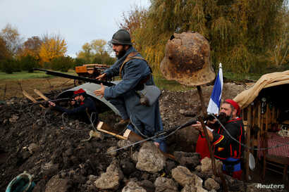History enthusiasts, members of French association Tempus Fugit, dressed in World War I French military outfits, re-enact daily life of soldiers during trench warfare, in Ecourt-Saint-Quentin, France, Nov. 9, 2018, ahead of the centennial commemorati...