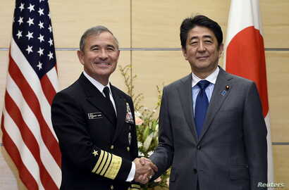 Japan's Prime Minister Shinzo Abe shakes hands with US Navy Admiral Harry B. Harris Jr., commander of the United States Pacific Command, before talks at Abe's official residence in Tokyo, Japan, Feb. 16, 2016.