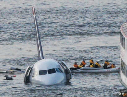 FILE - In this Jan. 15, 2009 file photo, passengers in an inflatable raft move away from an Airbus 320 US Airways aircraft that has gone down in the Hudson River in New York.