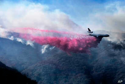 A firefighting DC-10 makes a fire retardant drop over a wildfire in the mountains near Malibu Canyon Road in Malibu, Calif., Nov. 11, 2018.
