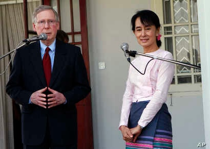 U.S. Senator Mitch McConnell, left, talks as Myanmar pro-democracy leader Aung San Suu Kyi listens during a press conference after their meeting at her home in Yangon, Myanmar, Jan. 16, 2012.
