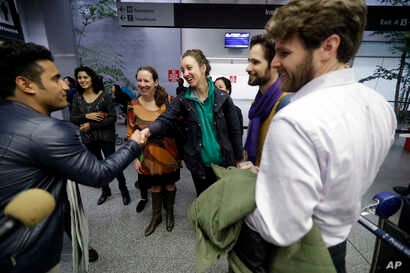 Former U.S. Army interpreter Qismat Amin, left, is greeted by supporters after arriving from Afghanistan at San Francisco International Airport, Feb. 8, 2017, in San Francisco. Amin waited nearly four years for his special immigrant visa.