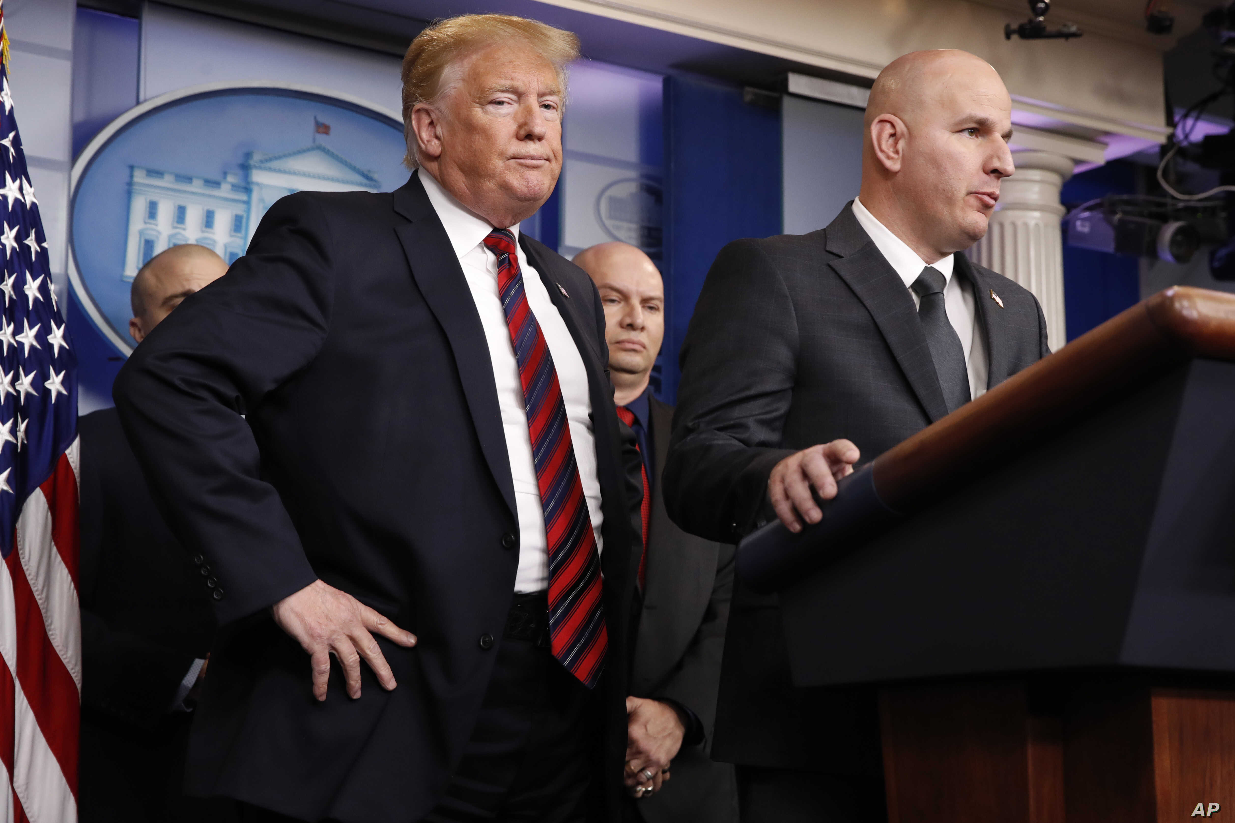 President Donald Trump, left, listens as Brandon Judd, president of the National Border Patrol Council, talks about border security, Jan. 3, 2019, after making a surprise visit to the press briefing room of the White House.