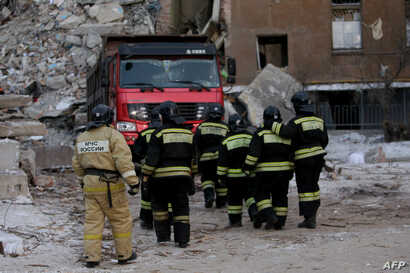 Firefighters are seen at the site of a gas explosion that rocked a residential building in Magnitogorsk, Russia, Jan. 2, 2019.