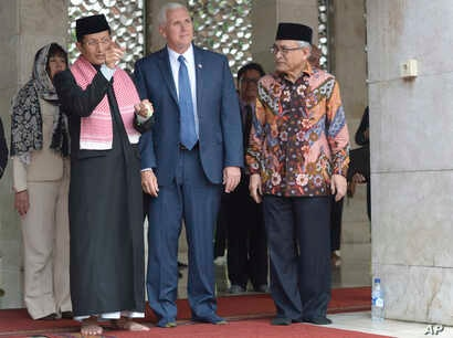 U.S. Vice President Mike Pence (center) is given a tour by the Grand Imam of Istiqlal Mosque Nasaruddin Umar (left) and the Chairman of the mosque Muhammad Muzammil Basyuni (right) during his visit to the largest mosque in Southeast Asia, in Jakarta,...