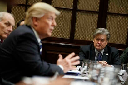FILE - White House Chief Strategist Steve Bannon listens at right as President Donald Trump speaks during a meeting on cyber security in the Roosevelt Room of the White House in Washington.