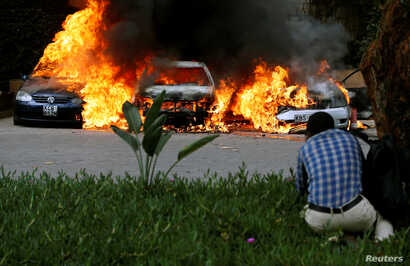 Cars are seen on fire at the scene of explosions and gunshots in Nairobi, Kenya January 15, 2019.