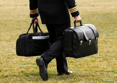 "A military aide, carrying the ""football"" containing launch codes for nuclear weapons, accompanies U.S. President Donald Trump onto Marine One upon Trump's departure from the White House in Washington,  Feb. 3, 2017."