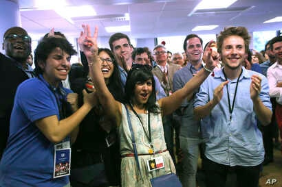 Macron's La Republique en Marche party members react after the announcement of the first partial official results and polling agencies projections are announced, in Paris, June 11, 2017.