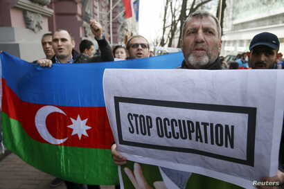 FILE - People hold up an Azerbaijani national flag and a sign during a rally in support of Azerbaijan over the conflict in the breakaway Nagorno-Karabakh region, outside the Armenian embassy in Kiev, Ukraine, April 8, 2016.