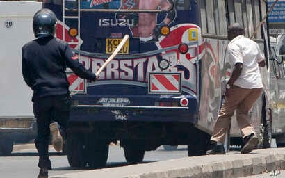 A riot policeman and an officer in plain clothes chase demonstrators who got into a bus near the IEBC, Independent Electoral and Boundaries Commission offices, in Nairobi, Kenya, Oct. 6, 2017.
