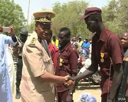 The Governor of Cameroon's far north region Midjiyawa Bakari greets a vigilante member. (ME Kindzeka  for VOA)