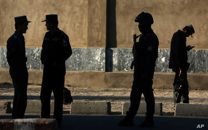 FILE - In this  Saturday, Feb. 27, 2016 file photo, Afghan National police stand at the site of a suicide attack near the Defense Ministry compound, in Kabul, Afghanistan. Senior members of the Afghan Taliban said on Thursday that a prominent figure ...