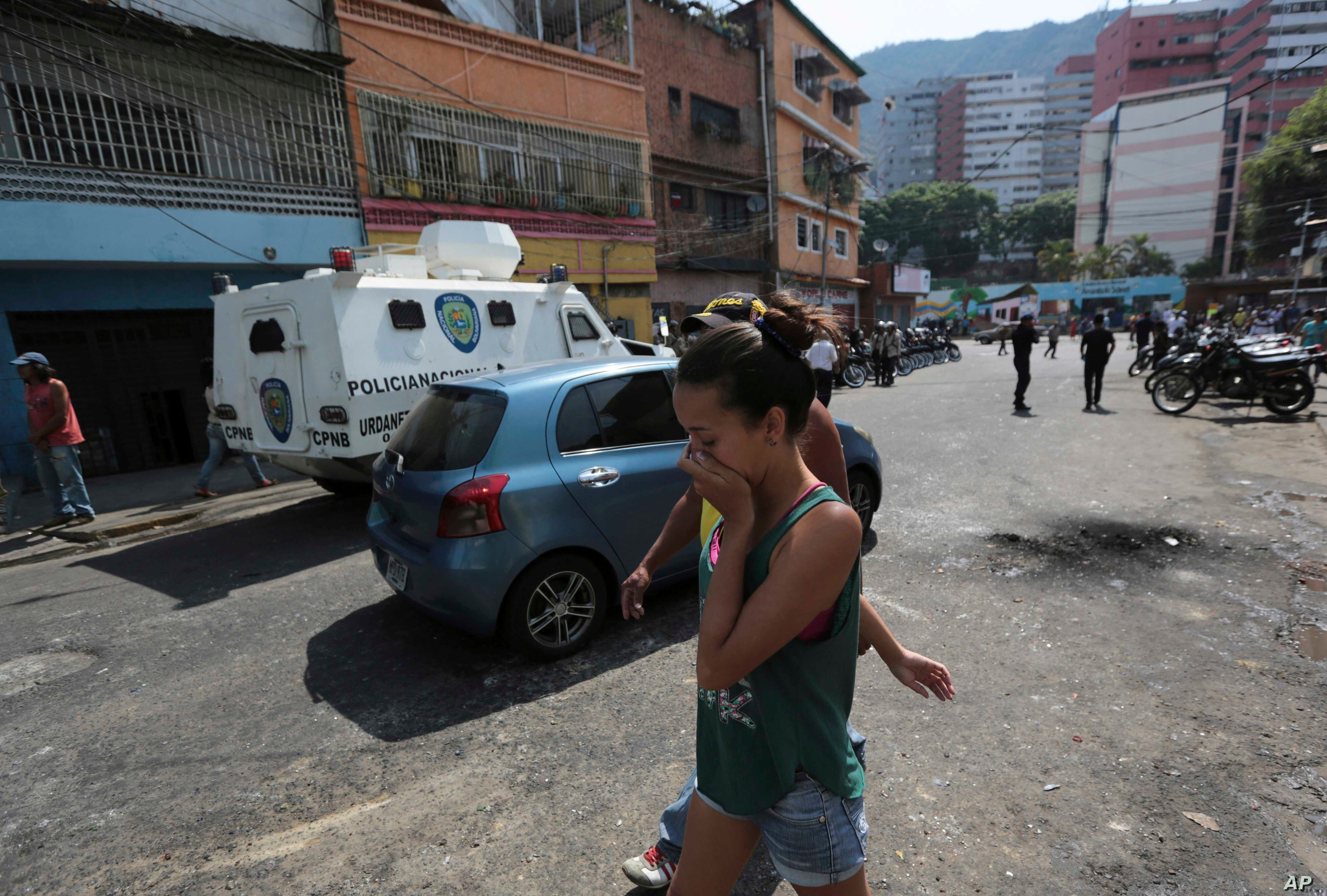 A resident covers her month from tear gas fired by Bolivarian National Police outside of a grocery and liquor store to disperse looters during a protest in Caracas, Venezuela, April 12, 2017.