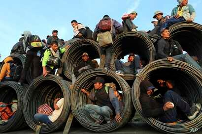 Central American migrants, part of the caravan hoping to reach the U.S. border, get a ride on a truck carrying rolls of steel rebar, in Irapuato, Mexico,  Nov. 12, 2018.