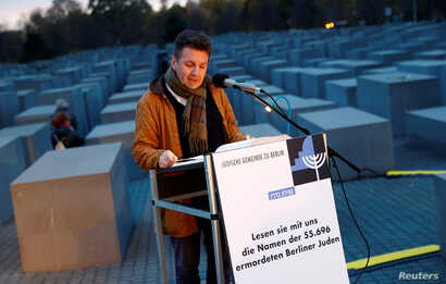 A volunteer of Berlin's Jewish community reads out all names of Jews killed in the city during the Holocaust at the Holocaust Memorial on the eve of the 80th anniversary of Kristallnacht, also known as Night of Broken Glass, a state-sponsored spree o...