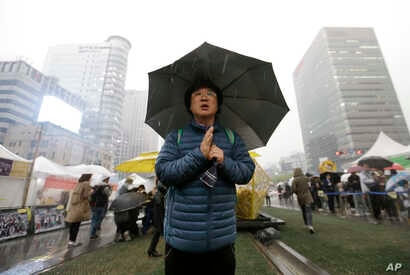 A mourner prays to pay tribute to victims of the sunken ferry Sewol outside a temporary memorial altar in Seoul, South Korea, Thursday, April 16, 2015. Tears and grief mixed with raw anger Thursday as black-clad relatives mourned the 300 people, most...