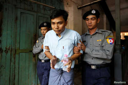 Detained Reuters journalist Kyaw Soe Oo is escorted by police before a court hearing in Yangon, Myanmar, Apr. 11, 2018