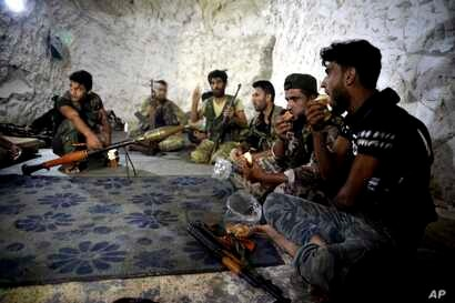 FILE - Fighters with the Free Syrian army eat in a cave where they live, in the outskirts of the northern town of Jisr al-Shughur, Syria, west of the city of Idlib, Sept. 9, 2018.