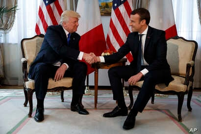 President Donald Trump shakes hands with French President Emmanuel Macron during a meeting at the U.S. Embassy, May 25, 2017, in Brussels.