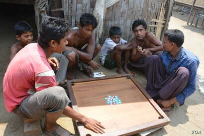 Displaced Rohingya men and boys play a Carrom board game in Baw Du Pha Camp 1 outside Sittwe. (P. Vrieze for VOA)