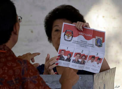 FILE - An election official explains to an elderly woman how to give her vote at a polling station in Jakarta, Feb. 15, 2017.